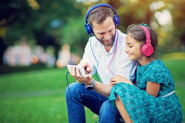 Father and daughter are listening the music in park stock photo
