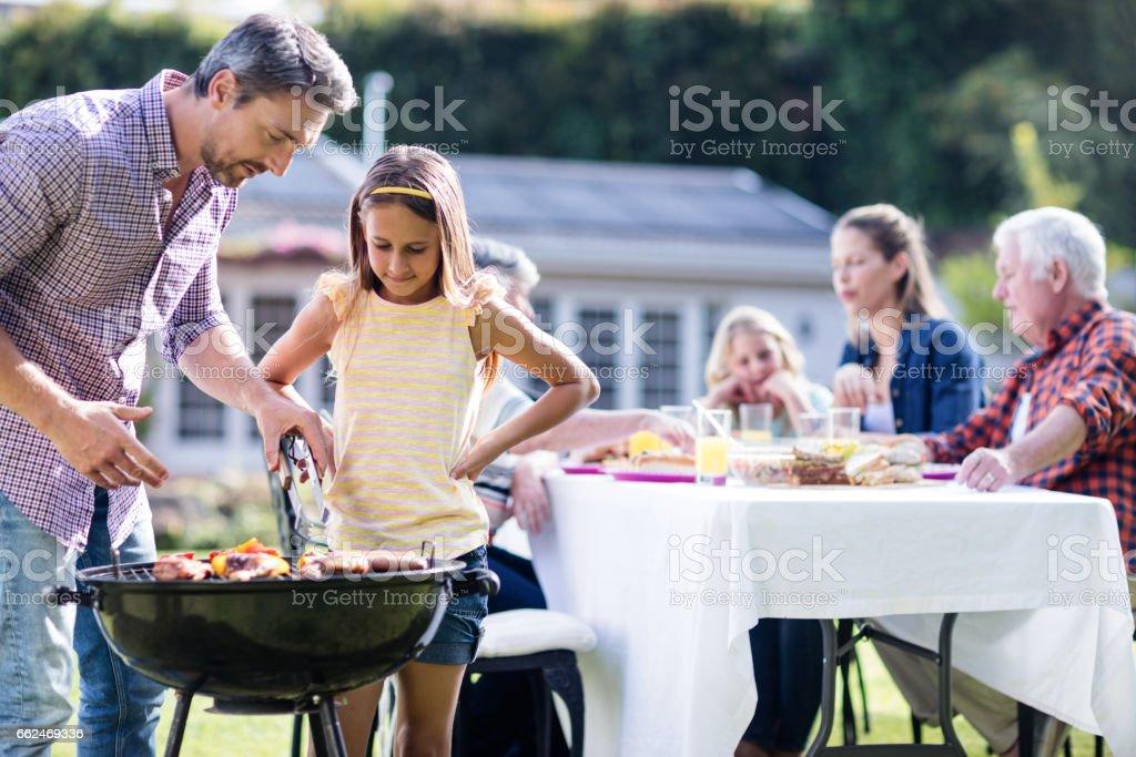 Père et fille au barbecue grill tout en déjeunant en fond de famille - Photo