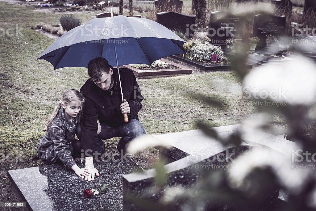 Father and daughter at graveyard visiting grave of mother stock photo