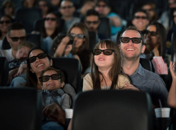 Father and daughter at the cinema wearing 3D glasses stock photo