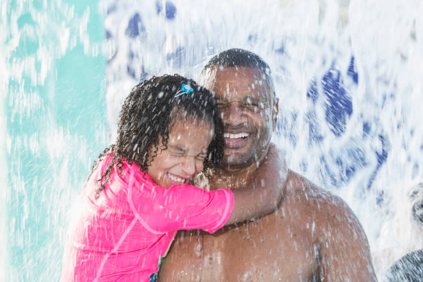 Father and daughter at water park getting splashed stock photo