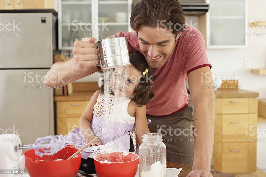 Father and daughter (2-4) baking, father sifting flour, smiling royalty-free stock photo