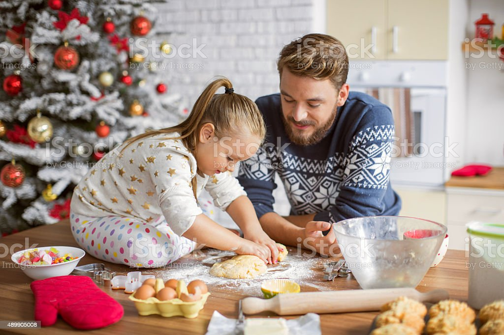 Father and daughter baking in kitchen for christmas. stock photo