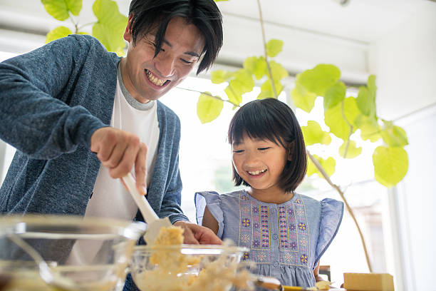 Father and daughter baking together stock photo