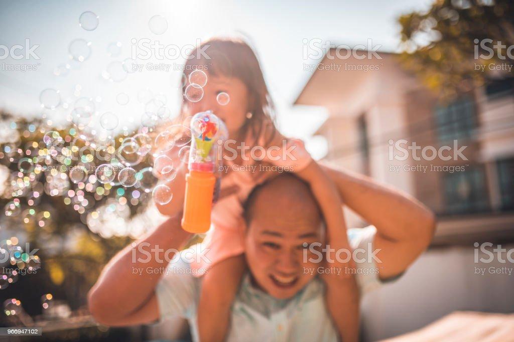 Vater und Tochter Seifenblasen im Hinterhof – Foto