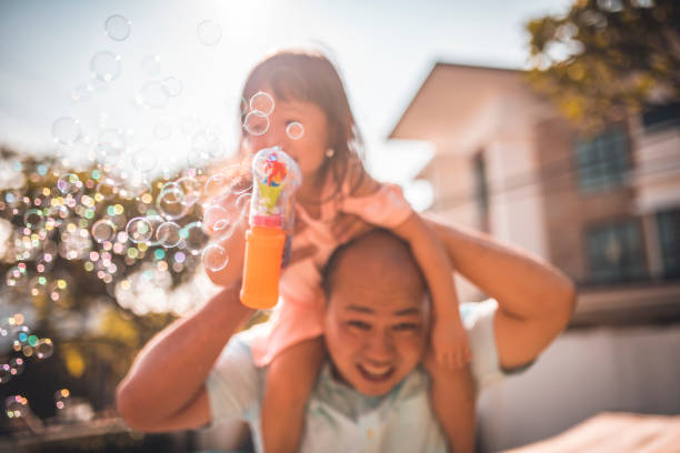 Father and daughter blowing bubbles in backyard stock photo