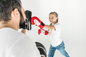cropped shot of father and smiling daughter boxing together isolated on white