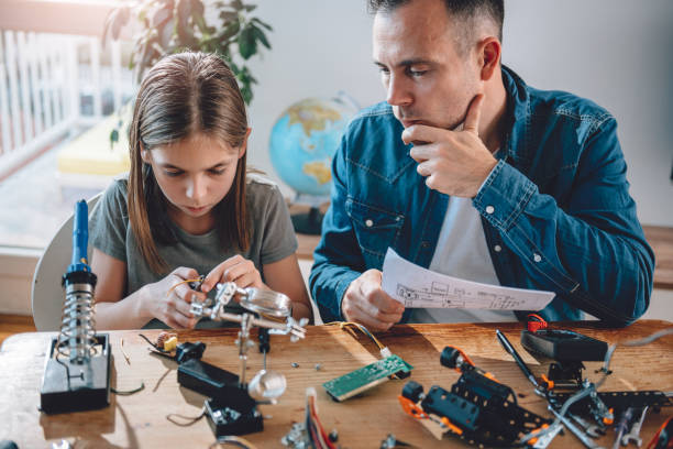 Father and daughter building robot Father and daughter sitting by the wooden table and building robot at home as a school science project soldering iron stock pictures, royalty-free photos & images
