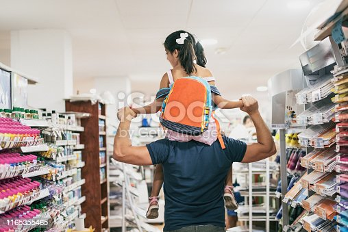 Father and daughter buying school supplies preparing to go back to school, preparing for september, girl on shoulders