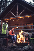 Father and daughter  chatting by the campfire at their cabin in the woods