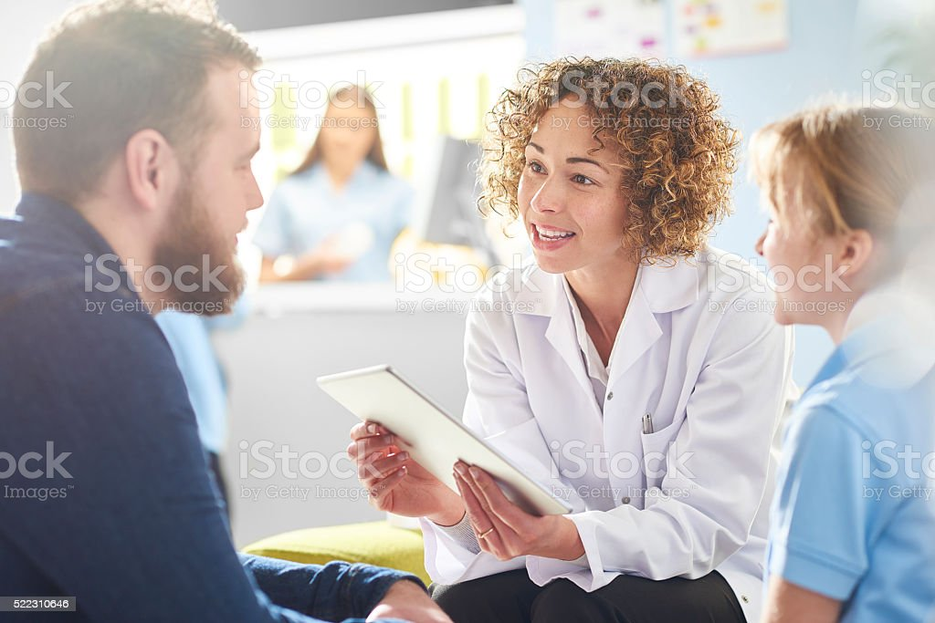 father and daughter chatting to pharmacist stock photo