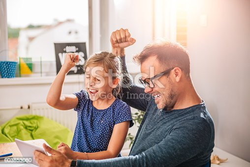 istock Father And Daughter Cheering during playing game on tablet 603853080