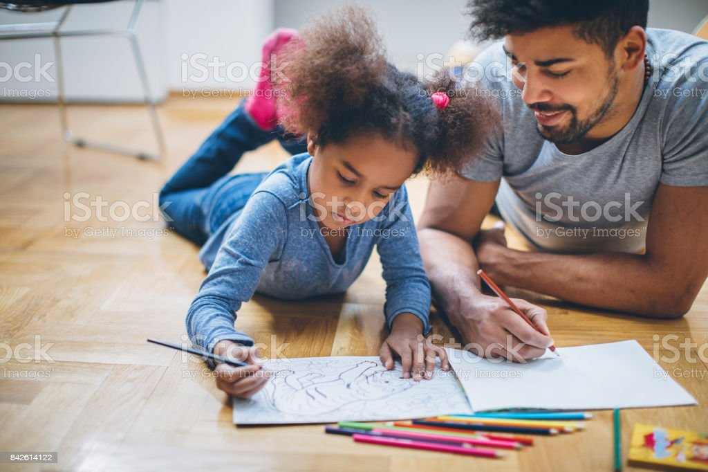 Father and daughter coloring together stock photo