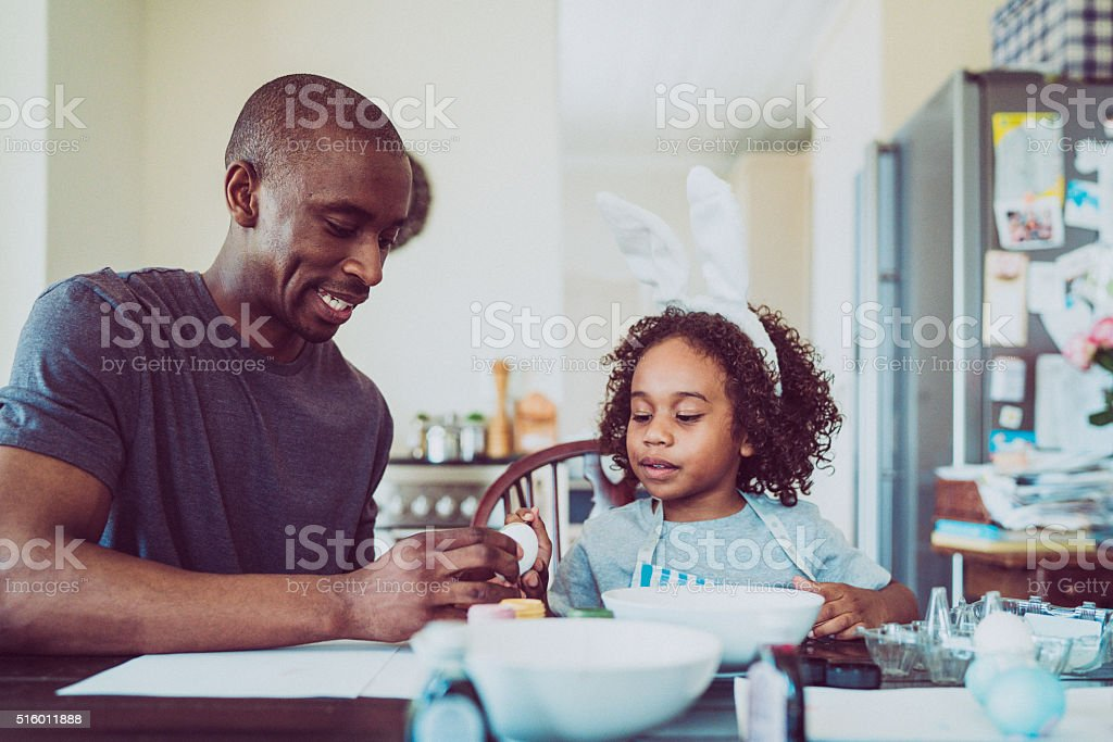 Father and daughter colouring egg for Easter royalty-free stock photo
