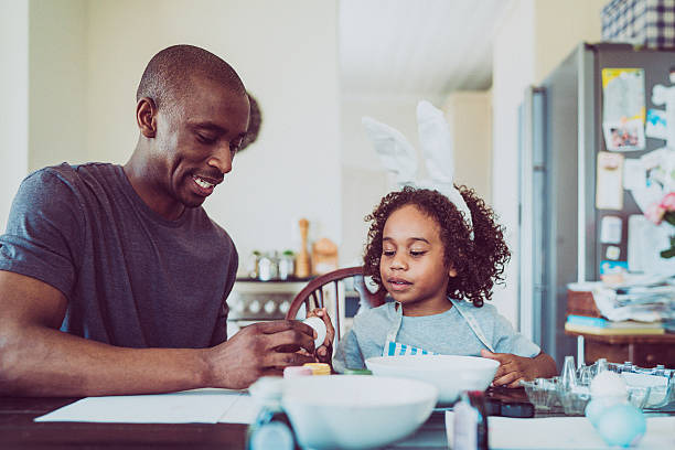 Father and daughter colouring egg for Easter stock photo
