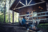 Father and daughter cooking marshmallows by the campfire at their cabin in the woods
