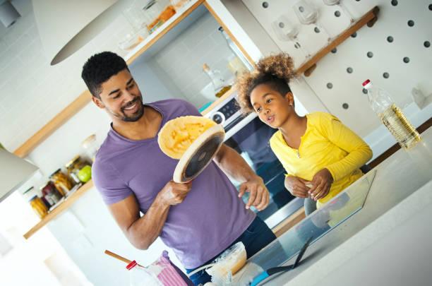 Vater und Tochter kochen zusammen während der Quarantäne. – Foto