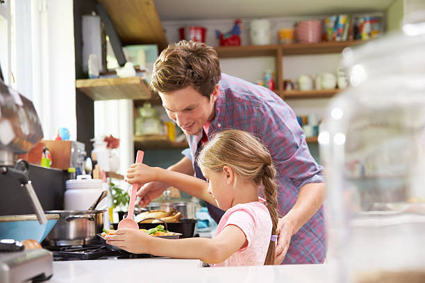 tochter hilft vater kochen essen in der küche - hausmannskost stock-fotos und bilder