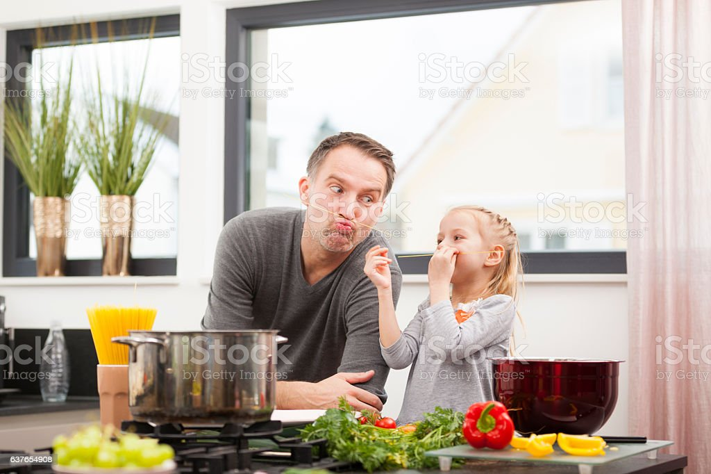 father and daughter cooking together stock photo