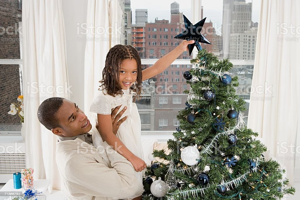 Father and daughter decorating Christmas tree royalty-free stock photo