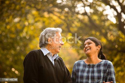 Father and daughter discussing and laughing at park