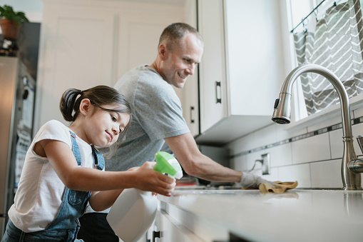 A little girl sprays disinfectant while her dad wipes up the counter wearing rubber gloves. Part of a regular routine, or the new normal with social distancing and working from home during the Covid-19 Pandemic.
