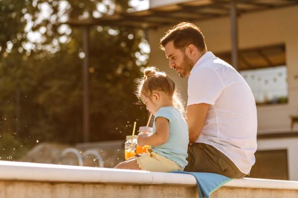 Vater und Tochter trinken frischen Saft am Pool – Foto