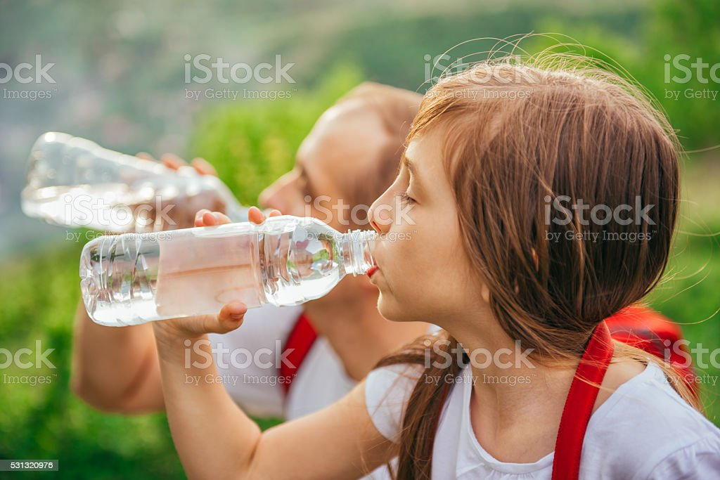 Father and daughter drinking water stock photo