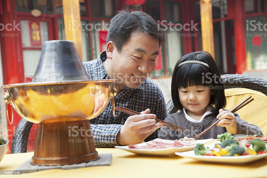 Father and daughter eating Chinese food outside stock photo