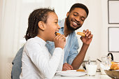 Sweet African American Girl And Her Dad Eating Cookies At Kitchen, drinking milk, side view