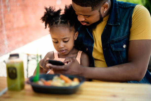 Father and daughter eating take out food outdoors. stock photo