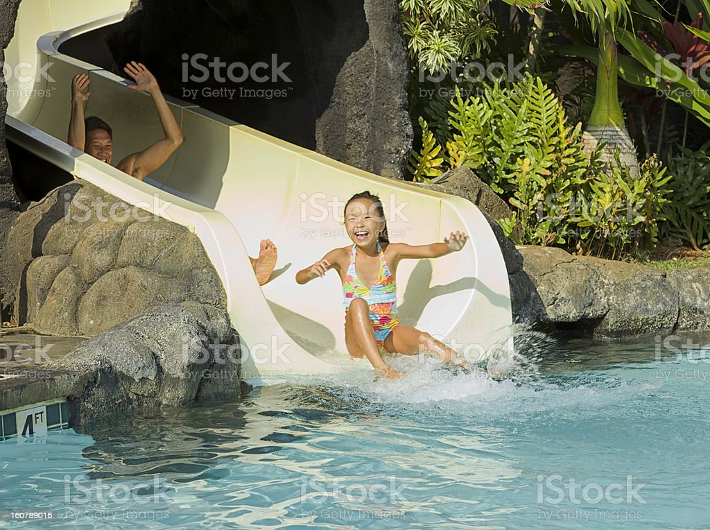 Father and Daughter enjoy sliding down the waterslide stock photo