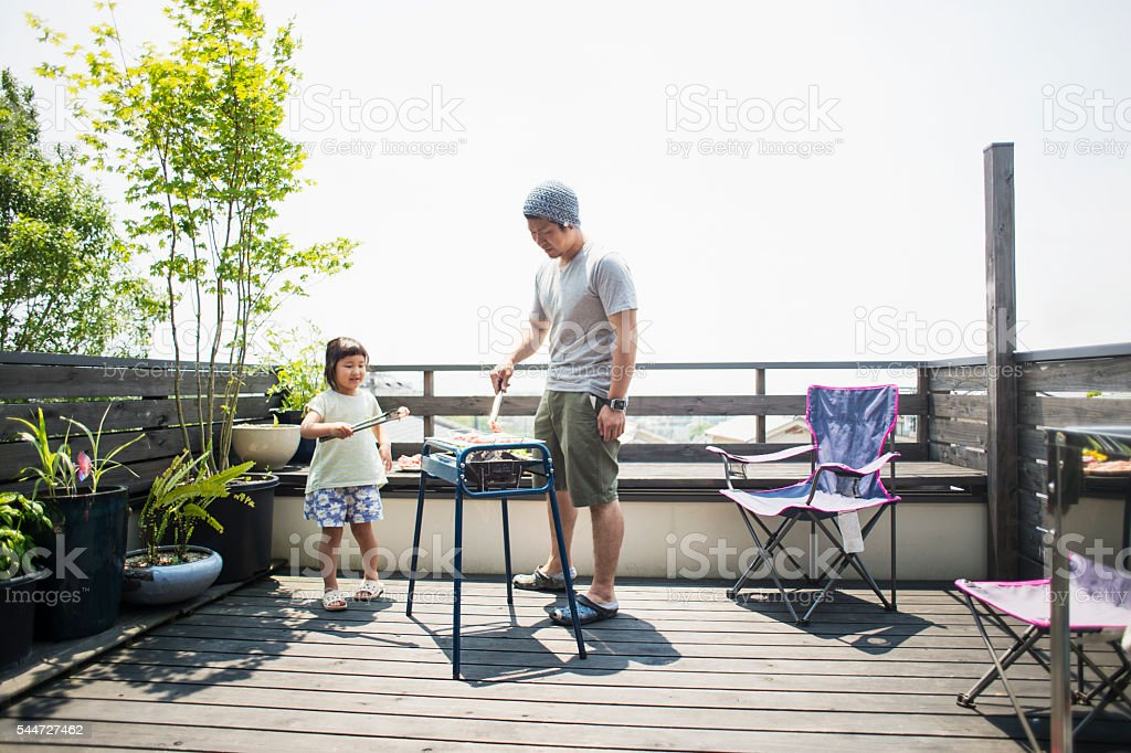 Father and daughter enjoying a barbecue on the terrace stock photo