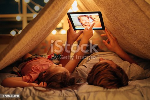Father and daughter enjoying at home. Lying on bed at night in do it yourself tent and using digital tablet together. Taking selfies and watching photos.