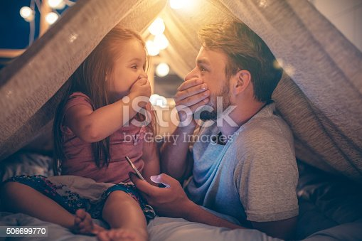 Father and daughter enjoying at home. Lying on bed at night in do it yourself tent and using smart phone together. Taking selfies and watching photos.