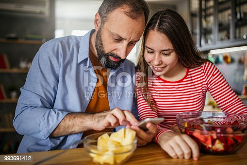 Photo of father with daughter surfing the net at the home