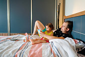 Father and daughter enjoying at home. Sitting on bed and reading book together