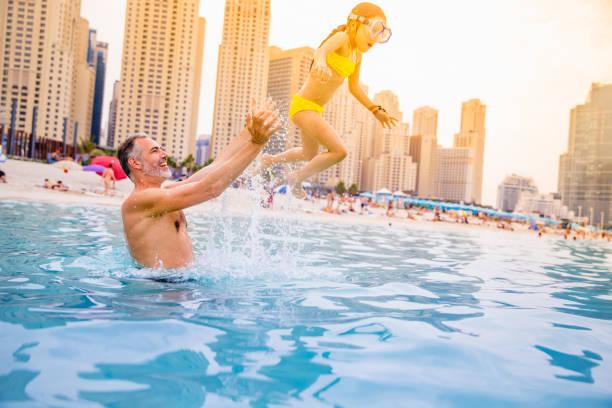 vater und tochter genießen am strand von dubai - dubai urlaub stock-fotos und bilder