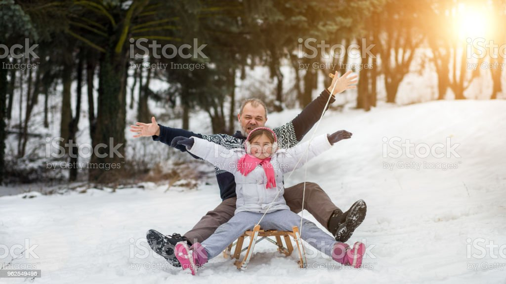 Father and daughter enjoying in snow stock photo