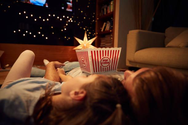 vater und tochter filmabend zu hause gemeinsam genießen - mädchen night snacks stock-fotos und bilder