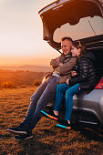 istock Father and daughter enjoying sunset while sitting in the car trunk 1170503787
