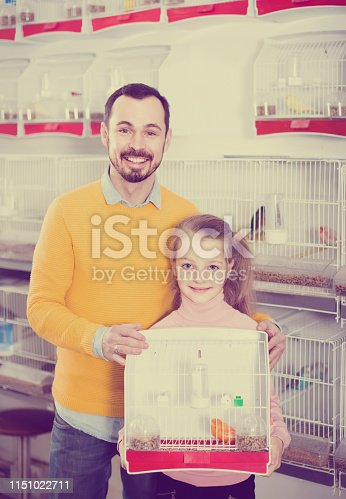 happy russian father and daughter enjoying their purchase of canary bird in pet shop
