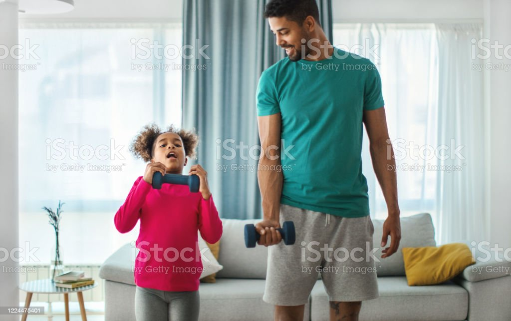 Father and daughter exercising at home. Closeup front view of a young african american man exercising at home. They are lifting some lightweight dumbbells. The girls is struggling with the exercise and desperately looking at th camera. 30-34 Years Stock Photo