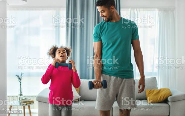 Father And Daughter Exercising At Home Stock Photo - Download Image Now