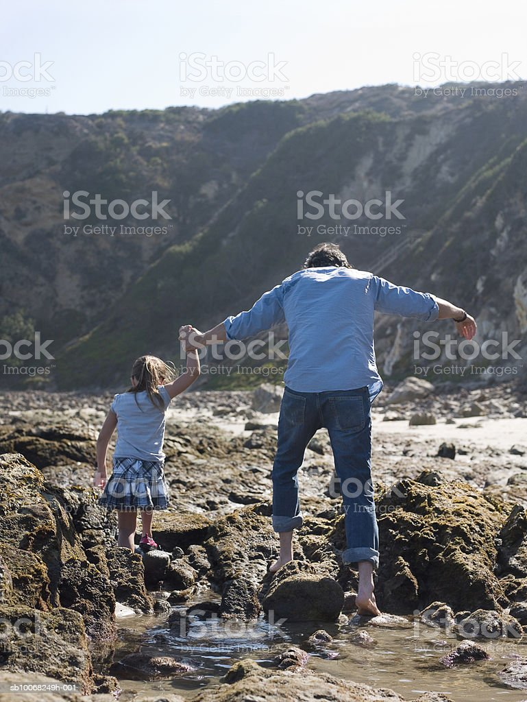Father and daughter (6-7) exploring seashore, rear view 免版稅 stock photo