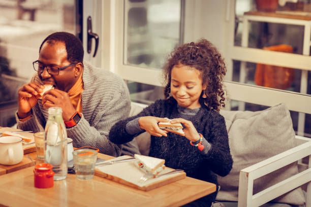 Father and daughter feeling satisfied while eating tasty sandwiches stock photo