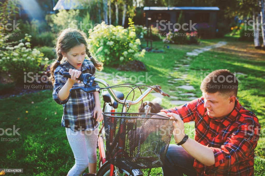 father and daughter fixing problems with bicycle outdoor in summer....