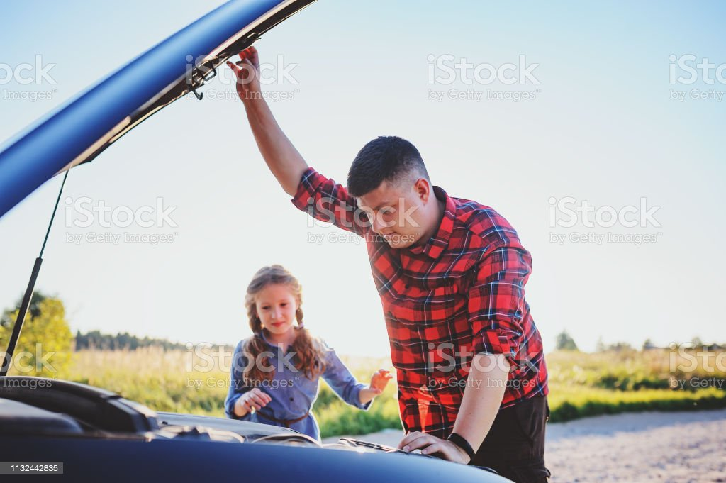 father and daughter fixing problems with car during summer road trip....