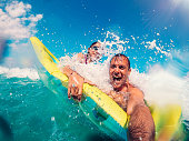 Father and daughter floating on the yellow air bed in the sea while getting splashed by the wave