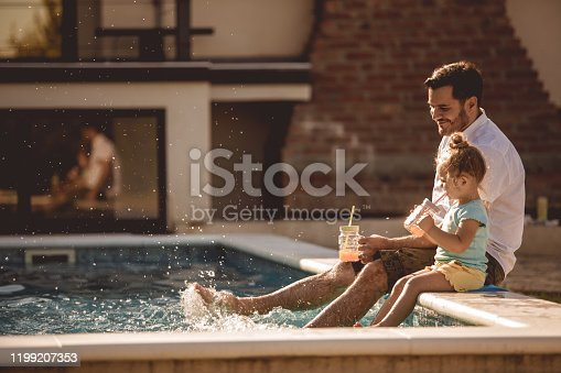 Side view of lovely scene where daughter and dad plunge their feet in a pool while drinking fresh juices.